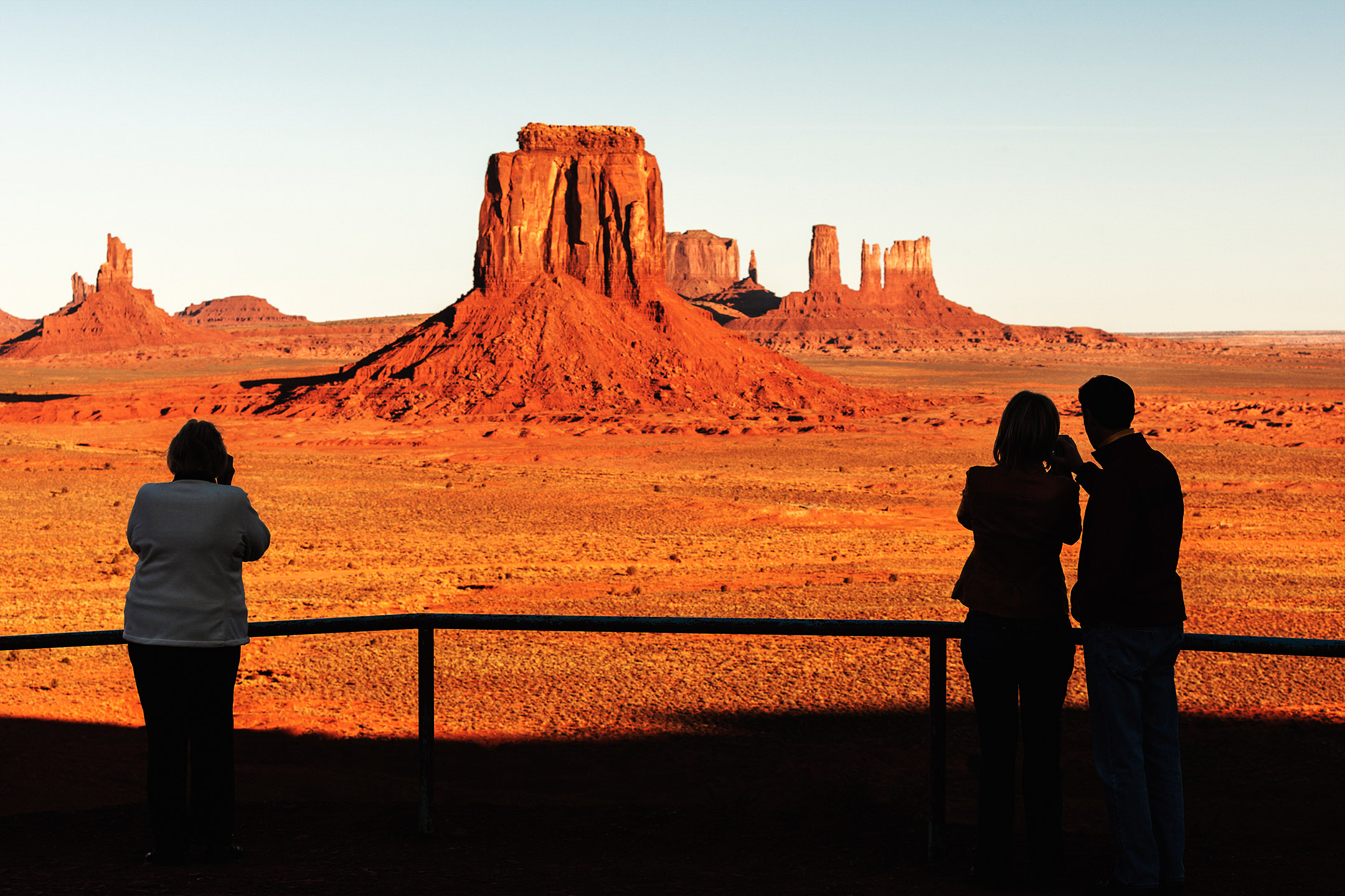Silhouetted people enjoying a sunrise view of Monument Valley, Navajo County, Arizona.